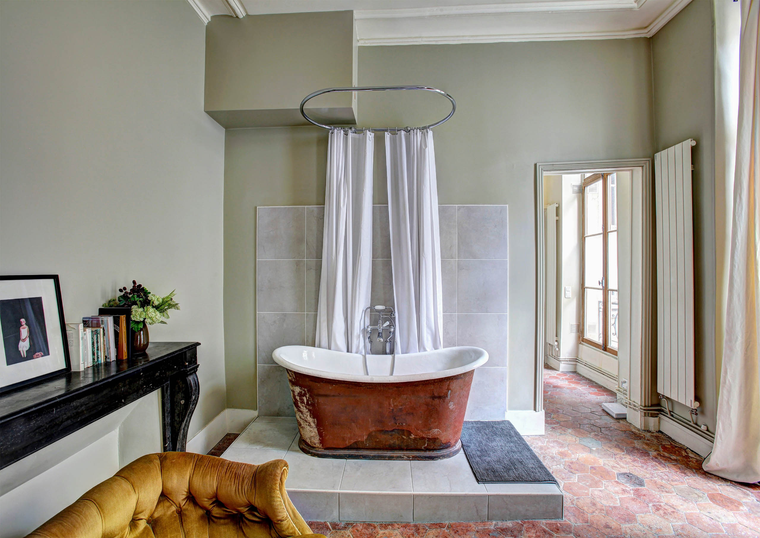 Renovated Bathroom with Pedestal Bathtub on Raised Marble